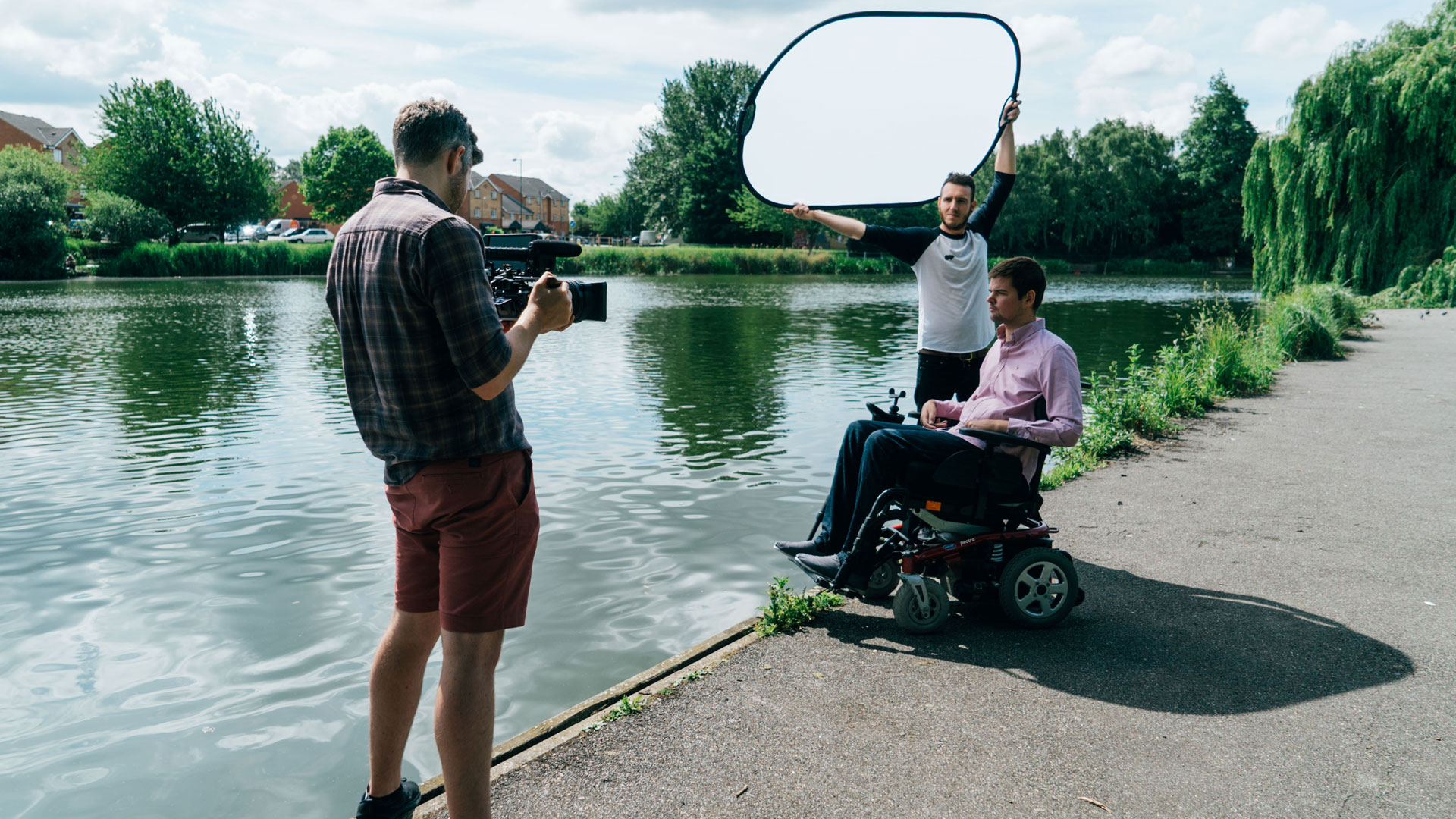 Small film crew, shooting with Michael (a wheelchair user) by a lake.